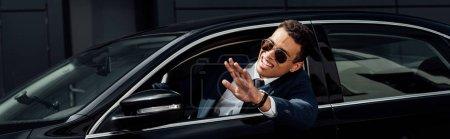 Photo pour Homme d'affaires afro-américain en costume et lunettes de soleil agitant la main de la voiture à la journée ensoleillée, vue panoramique - image libre de droit