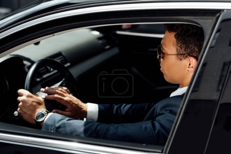 Photo for African american businessman in suit and sunglasses beeping in car at sunny day - Royalty Free Image