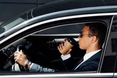 Photo pour Vue latérale d'un homme d'affaires afro-américain en costume et lunettes de soleil conduisant une voiture et buvant du café le jour ensoleillé - image libre de droit