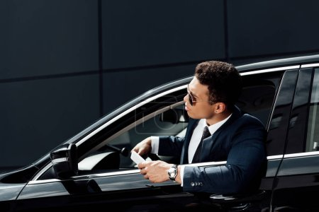 Photo for African american businessman in suit and sunglasses looking out from from car at sunny day - Royalty Free Image
