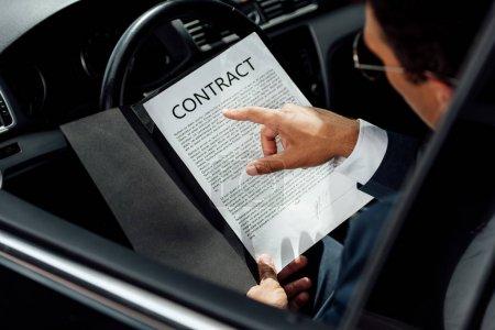Photo pour Vue recadrée de l'homme d'affaires américain africain dans le contrat de lecture de procès dans la voiture au jour ensoleillé - image libre de droit