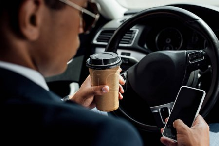 Photo for Back view of african american businessman in suit and sunglasses using smartphone and drinking coffee in car - Royalty Free Image