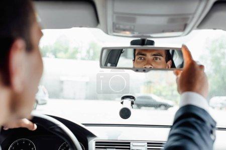 Photo pour Homme d'affaires américain africain dans la voiture de conduite de procès et regardant le miroir - image libre de droit