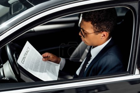 Photo for African american businessman in suit reading contract in car - Royalty Free Image