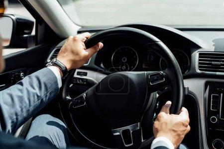 Photo pour Vue partielle de l'homme d'affaires afro-américain en costume voiture de conduite - image libre de droit