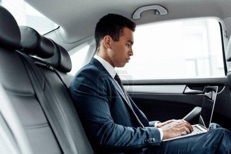 Photo pour Vue latérale de l'homme d'affaires américain africain utilisant l'ordinateur portatif dans la voiture - image libre de droit