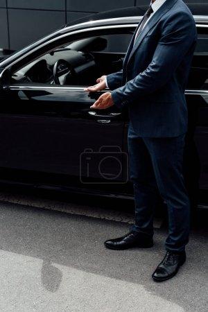 Photo pour Vue recadrée de l'homme afro-américain en costume pointant vers la porte de la voiture - image libre de droit