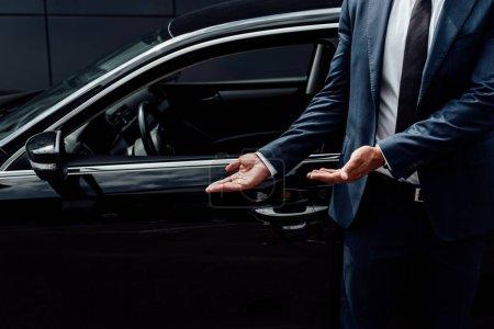 Photo pour Vue recadrée de l'homme afro-américain en costume pointant vers la porte de voiture noire - image libre de droit