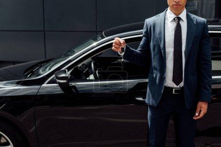 Photo pour Vue recadrée de l'homme américain africain dans la clef de voiture de fixation de procès - image libre de droit