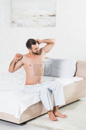 Foto de Hombre guapo que se estira en la cama durante la mañana en el dormitorio - Imagen libre de derechos