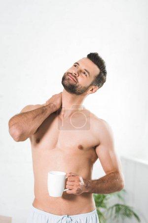 Photo pour Bel homme torse nu retenant la tasse de café à la maison le matin - image libre de droit