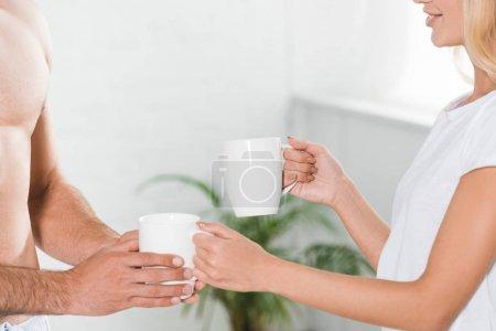 abgeschnittene Ansicht von Paar mit Kaffeetassen zu Hause am Morgen