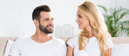 Photo pour Tir panoramique de beau couple en pyjama regardant les uns les autres sur le lit à la maison - image libre de droit
