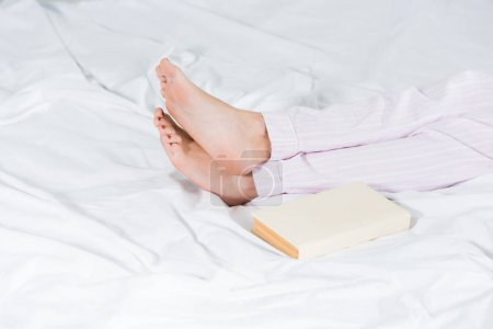 Photo for Cropped view of man in pajamas lying in bed near book - Royalty Free Image