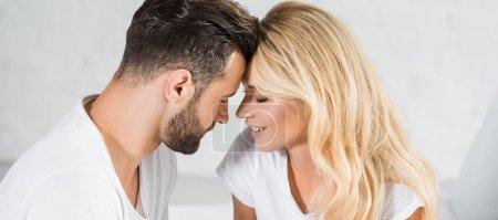 Photo pour Plan panoramique de beau couple en t-shirts blancs touchant les fronts à la maison - image libre de droit