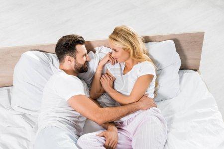 Photo pour Vue grand angle de beau couple couché au lit et étreignant à la maison - image libre de droit