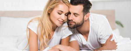 Photo pour Tir panoramique de beau couple avec les yeux fermés reposant sur le lit à la maison - image libre de droit
