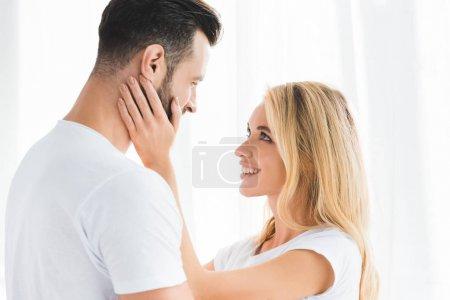 beau couple romantique embrassant à la maison près de la fenêtre