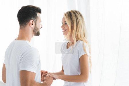 schönes glückliches Paar im Pyjama Händchen haltend zu Hause