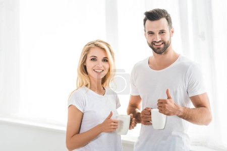 beautiful couple with coffee cups showing thumbs up at home in morning