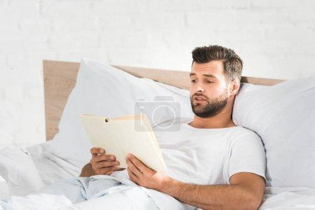 Photo pour Bel homme couché au lit et lisant le livre le matin - image libre de droit