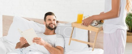 Photo for Panoramic shot of woman bringing breakfast to man in bed in morning - Royalty Free Image