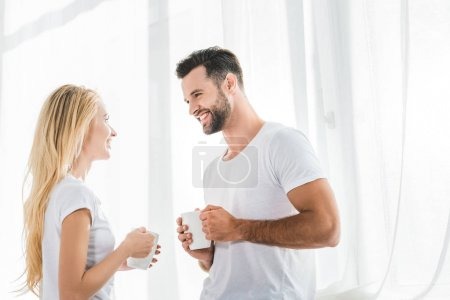 Photo for Beautiful couple with coffee cups looking at each other at home in morning - Royalty Free Image