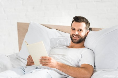 Photo for Handsome happy man lying in bed and reading book in morning - Royalty Free Image