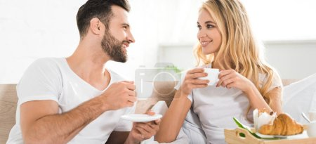 panoramic shot of beautiful couple with cups during breakfast in bed in morning