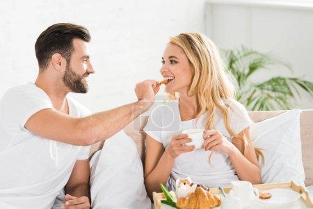 Photo pour Beau couple dans des pyjamas ayant le petit déjeuner dans le lit le matin - image libre de droit