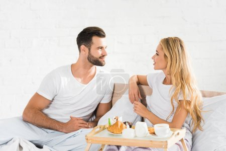 Photo for Beautiful couple in pajamas having breakfast in bed in morning - Royalty Free Image