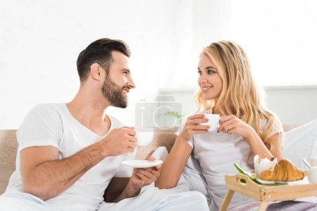 Photo for Beautiful couple with cups during breakfast in bed in morning - Royalty Free Image