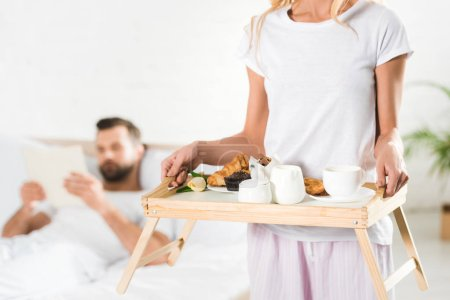 Photo for Cropped view of woman holding food tray with breakfast in bedroom - Royalty Free Image