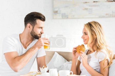 beautiful couple having breakfast in bed in morning