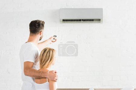 Photo pour Vue arrière du couple avec télécommande souffrant de chaleur sous climatiseur à la maison - image libre de droit