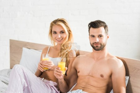 Photo pour Couple en pyjama avec du jus d'orange au lit le matin - image libre de droit