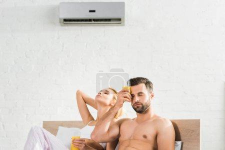 Photo pour Couple avec le jus d'orange souffrant de chaleur sous le climatiseur dans le lit à la maison - image libre de droit