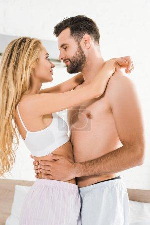 Photo pour Beau couple romantique regardant l'un l'autre et étreignant à la maison - image libre de droit