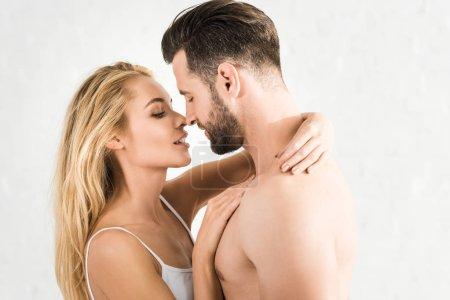 Photo pour Jeunes couples romantiques étreignant à la maison le matin sur le blanc - image libre de droit