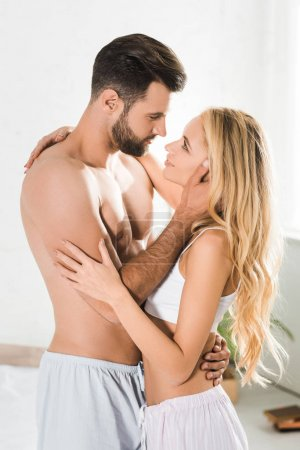 Photo for Beautiful romantic couple looking at each other and hugging at home - Royalty Free Image