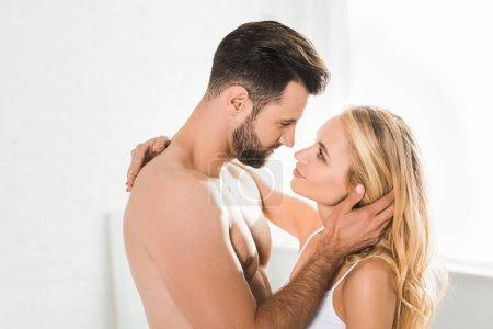 Photo pour Beau couple romantique regardant l'un l'autre et embrassant à la maison - image libre de droit