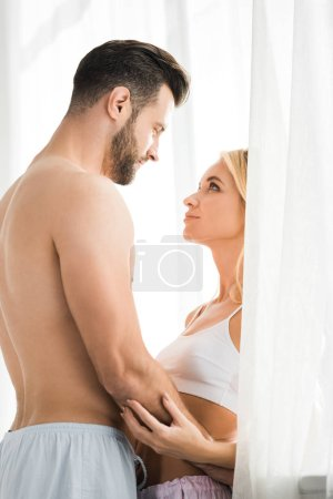 Photo for Beautiful romantic couple looking at each other and embracing at home - Royalty Free Image