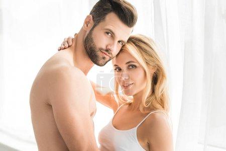 Photo pour Beau jeune couple romantique regardant l'appareil-photo et étreignant à la maison - image libre de droit
