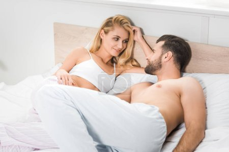 Photo for Beautiful couple lying in bed and looking at each other at home - Royalty Free Image