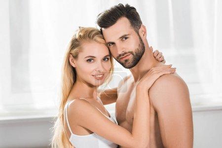 Photo pour Beau couple romantique regardant l'appareil-photo tout en étreignant à la maison - image libre de droit