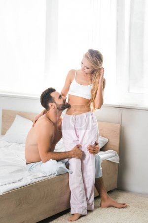 Photo pour Homme torse nu embrassant la belle femme à la maison le matin - image libre de droit