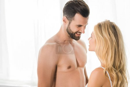 Photo for Handsome smiling shirtless man looking at woman at home - Royalty Free Image