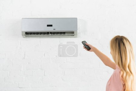 beautiful woman suffering from heat and holding remote control under air conditioner at home