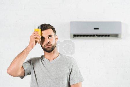 Photo pour Homme tenant du jus d'orange près du front et souffrant de chaleur sous climatiseur à la maison - image libre de droit
