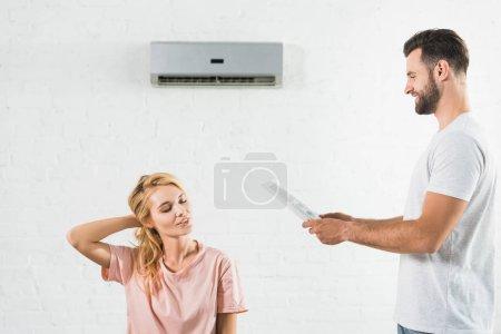 Photo pour Couple souffrant de chaleur sous climatiseur à la maison - image libre de droit